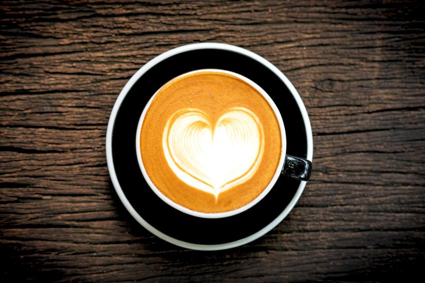 Heart shape latte art coffe in black cup on old wooden desk , top view