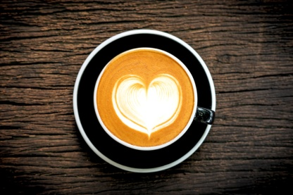 Heart shape latte art coffe in black cup on old wooden desk , top view